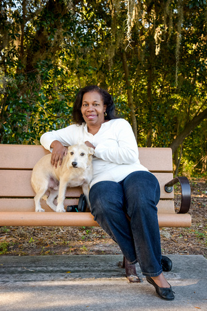 Woman sits with her dog in the park